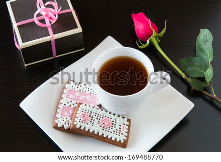 Cup of tea with homemade gingerbread cookies, red rose and a gift box. - stock photo