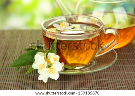 Cup of tea with jasmine, on bamboo mat, on bright background - stock photo