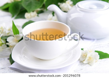 Cup of tea with jasmine on table close-up