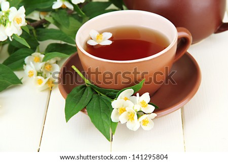 Cup of tea with jasmine, on wooden table, close-up