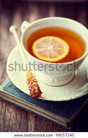 Cup of Tea with Lemon and Sugar Stick on a Old Book - stock photo