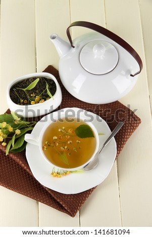 Cup of tea with linden on napkin on   wooden table