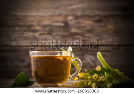 cup of tea with linden on wooden background - stock photo