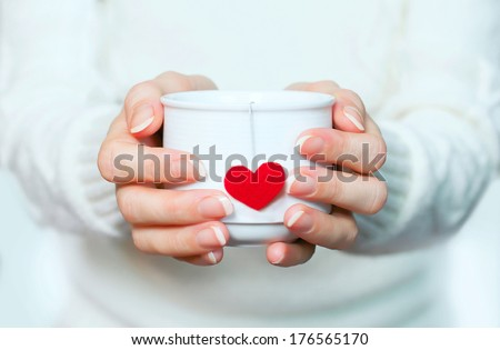 cup of tea with love in hands, red  heart teabag. - stock photo