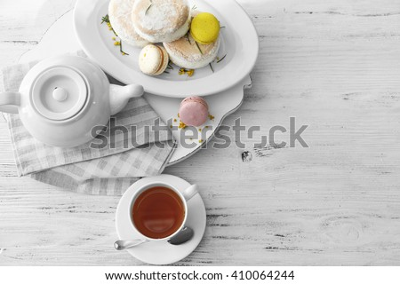 Cup of tea with macaroons on wooden background - stock photo