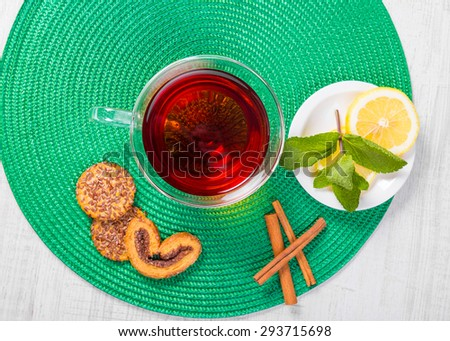 Cup of tea with mint, cinnamon and lemon. - stock photo