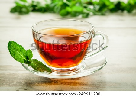 Cup of tea with mint on leaves wooden table. - stock photo