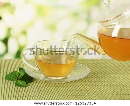 Cup of tea with mint on table on bright bacground