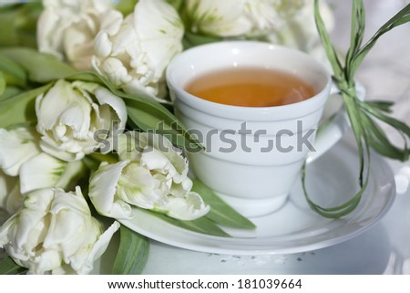 Cup of tea with spring flowers in a sunlight