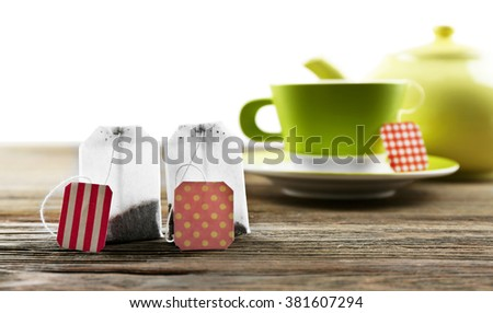 Cup of tea with tea bags and teapot on wooden background against grey background - stock photo