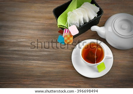 Cup of tea with tea bags and teapot on wooden table background - stock photo