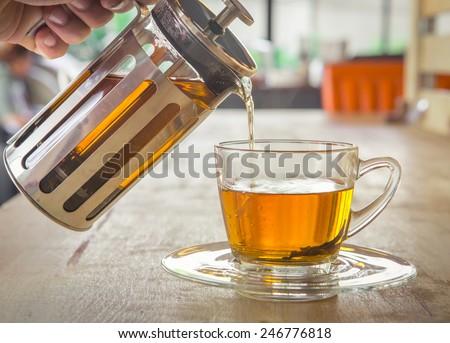 Cup of tea with tea pot - stock photo