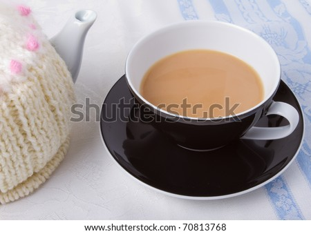 Cup of tea with tea pot and knitted tea cosy. - stock photo