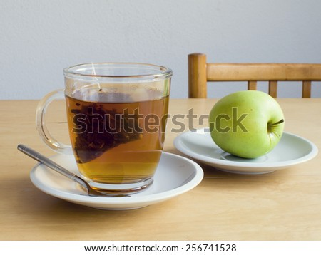Cup of tea with teabag and a green apple on a plate on table, snack time. - stock photo