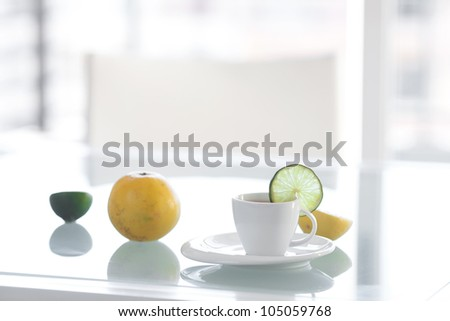 cup of tea with tropical fruits on a glass surface - stock photo