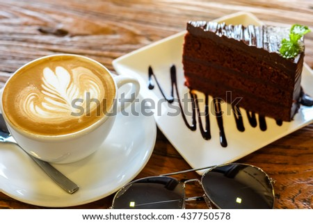 cup of the latte art coffee with spoon and plate on the brown bark beautiful texture background with warm light decorated with sunglasses and piece of chocolate fudge cake  - stock photo