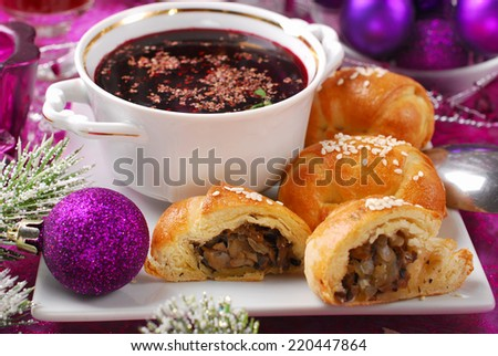 cup of traditional red borscht and yeast pastries with mushrooms filling for christmas eve - stock photo