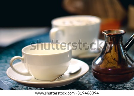 Cup of turkish coffee with turk on the table in cafe or coffee shop. Brown caffeine drink. Aroma hot black espresso, cappuccino with foam on breakfast in the morning in restaurant. Fresh latte.   - stock photo
