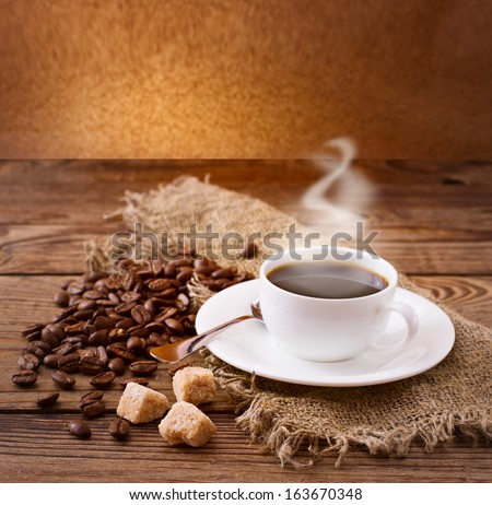 Cup of warm coffee, coffee beans and sugar cubes on  wooden surface. Free space for your text.