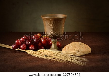 Cup of wine, red grapes, bread and wheat as symbols of Communion - stock photo