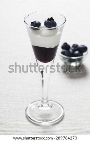 Cup of yogurt with blueberry jam and some decorative blueberries on a white tablecloth. There is a bowl of blueberries in the background with low depth of field. - stock photo