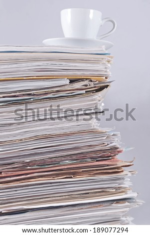 Cup on a pile of papers against a gray background - stock photo