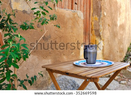 cup on a wooden table in a courtyard on background ocher facade - stock photo