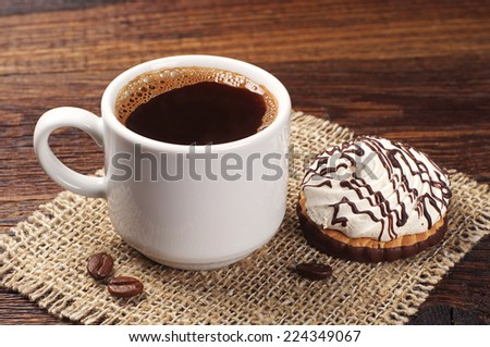 Cup on hot coffee and cookies with cream on old wooden table