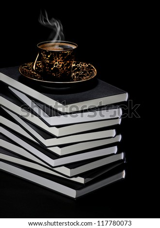 Cup or hot coffee with steam placed on top of large pile of books on black background