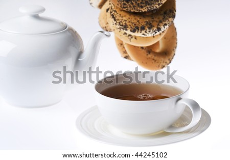 cup pf tea, teapot and bunch of traditional bagels - stock photo