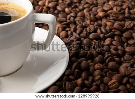 cup, saucer with spoon and coffee beans on wooden table - stock photo