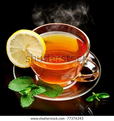 Cup tea with mint and lemon isolated on a black background. - stock photo
