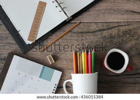 Cup white pencil, eraser, sharpener, calendar, address book, a cup of coffee on the desk. - stock photo