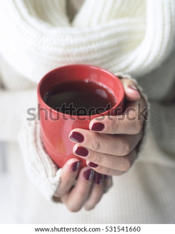 Cup with a hot drink in female hands close up. Soft style toned photo.