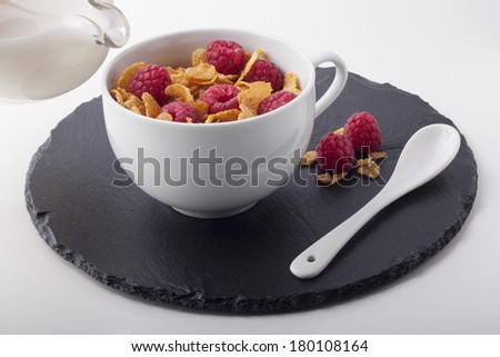 Cup with cereals and raspberries near to a milk jug - stock photo