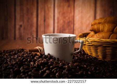 cup with coffee and coffee beans close up on a wood background