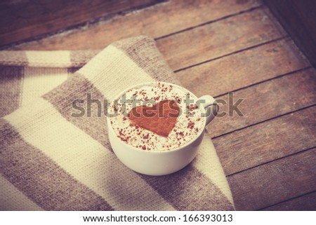 Cup with coffee and shape of the cacao heart on it and scarf. Photo with vintage vignetting.