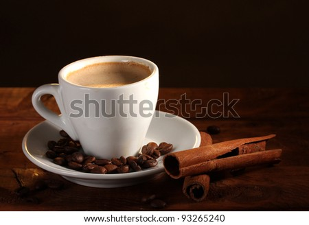 cup with coffee, cinnamon and coffee beans on  wooden table on brown background