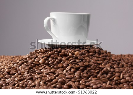 Cup with coffee, costing on coffee grain - stock photo