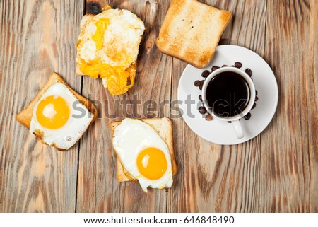 Cup with coffee, toast and eggs on a wooden table