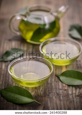 Cup with green tea and green leaves - stock photo