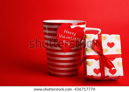 Cup with greeting card and gift box for Valentines Day on red background - stock photo