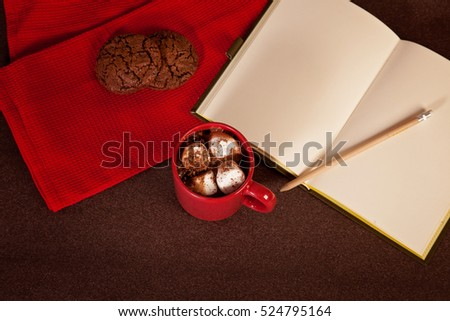 Cup with hot chocolate and open notebook