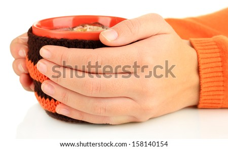 Cup with knitted thing on it in female hands isolated on white