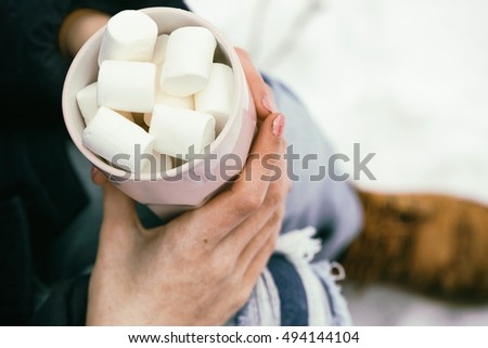 cup with marshmallows  in female hands