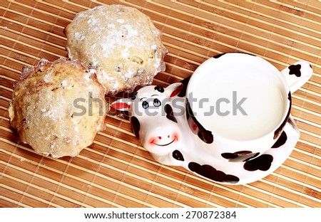 Cup with milk and tasty fruitcakes - stock photo
