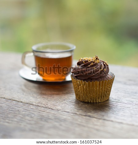 Cupcake and cup of tea on wooden table. Green background. Selective DOF. - stock photo