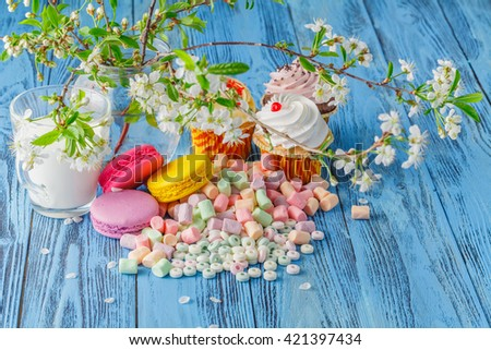 Cupcake and macaroons, marshmallow on the table among spring blooming