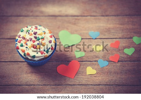 Cupcake and paper hearts on wooden background. - stock photo