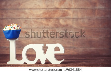 Cupcake and word Love on wooden table. - stock photo